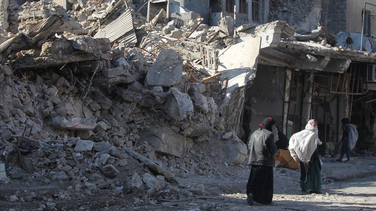 Unas mujeres caminan entre las ruinas de una calle de Mosul.