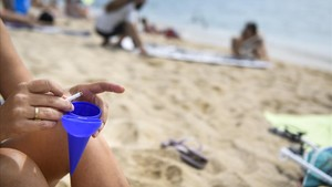 Una mujer deposita la ceniza del cigarro en un cenicero, en la playa de Ocata de El Masnou.