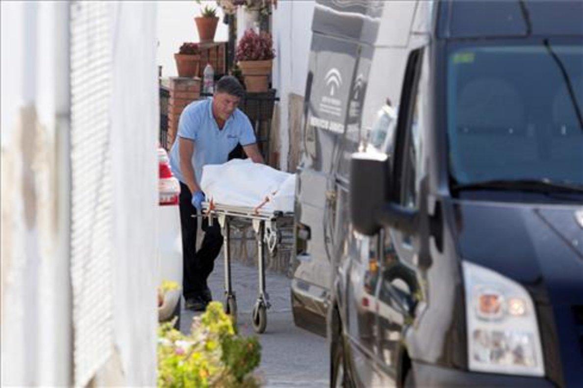 Un operario traslada al furgón fúnebre uno de los cadáveres hallados este miércoles en la localidad malagueña de Cortes de la Frontera.