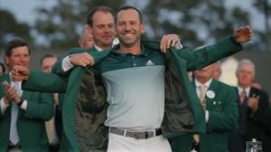 Sergio García se enfunda la chaqueta verde ayudado por Danny Willett, campeón del año pasado.