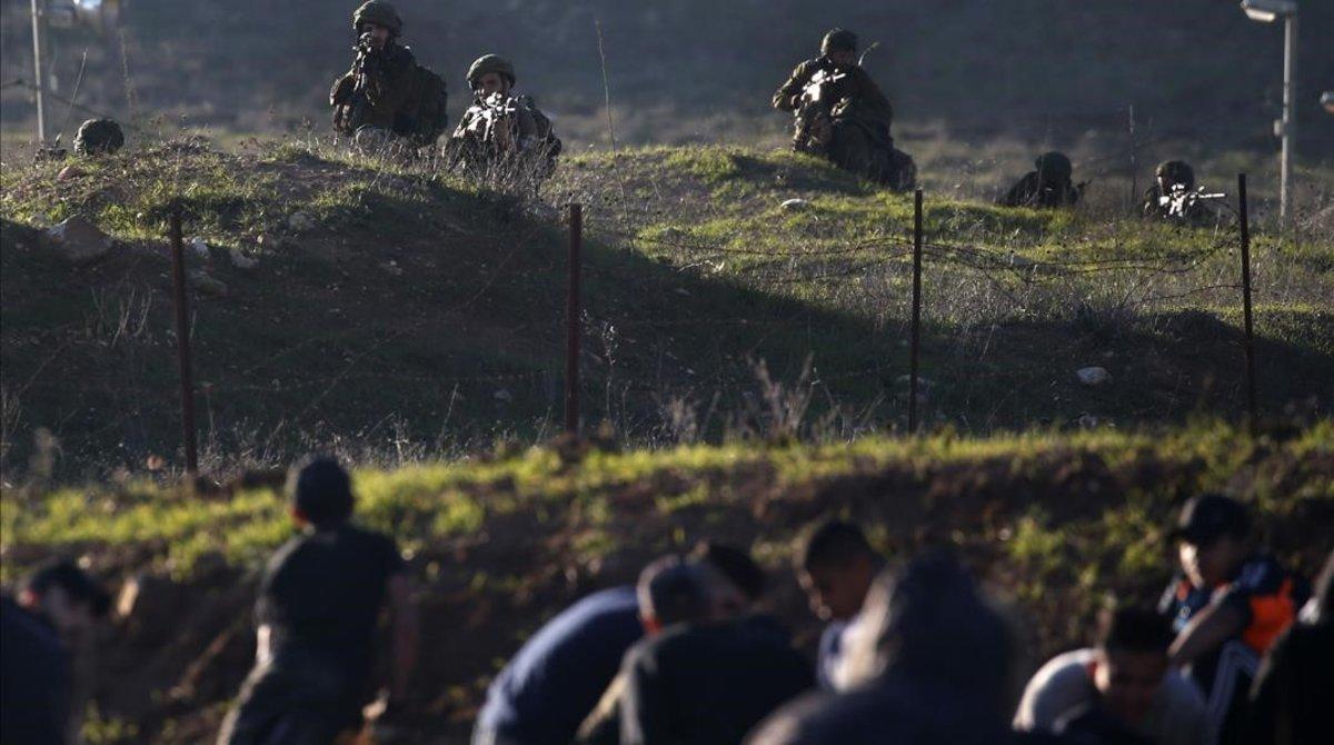 Soldados israelís y civiles palestinos, separaldos por la valla de seguridad cerca de Nablús, en Cisjordania.