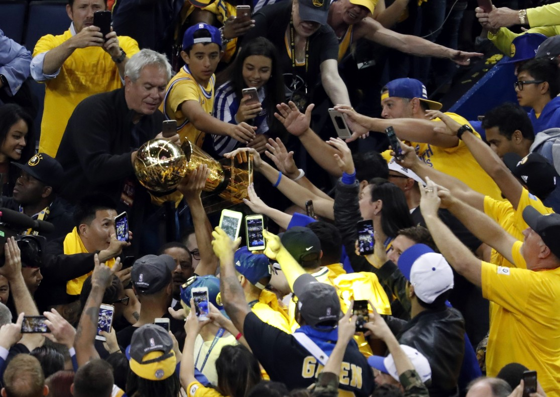 Stephen Curry alza el trofeo de la NBA.
