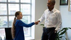 Greta Thunberg y Barak Obama chocan los puños, este miércoles.
