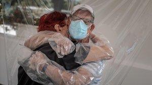 Una interna en una residencia de mayores abraza a su sobrino a través de un plástico.