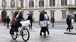 Una mujer pasea en bici, con mascarilla, por Milán.