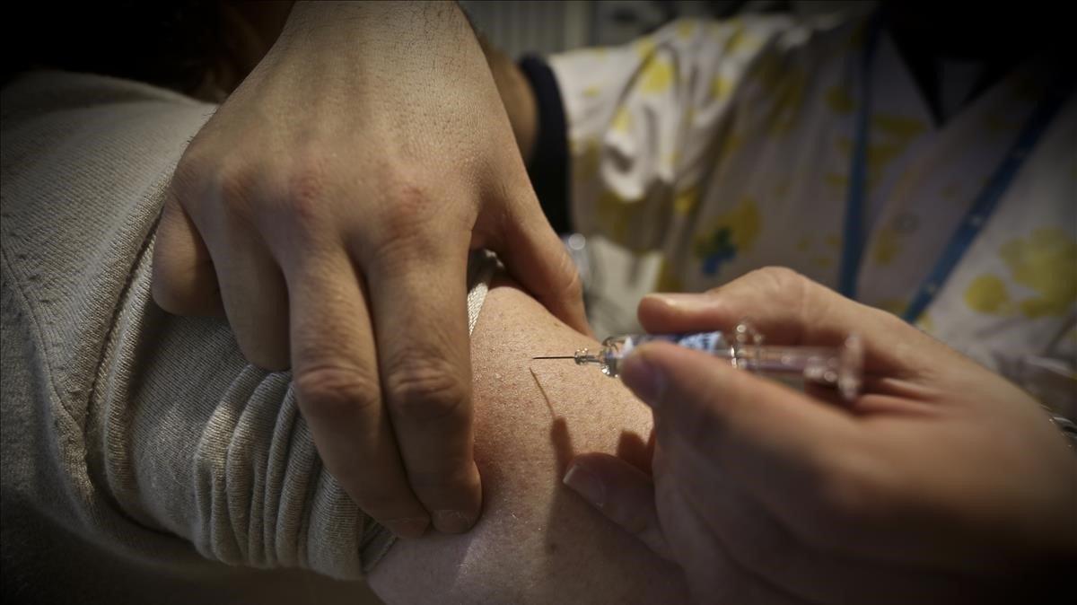 Una enfermera pone una vacuna de gripe, en una foto de archivo.