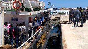 Varios inmigrantes rescatados en alta mar se disponen a desembarcar en el puerto italiano de Lampedusa.
