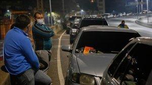 Venezolanos haciendo cola para llenar el depósito de gasolina del coche, el miércoles en Caracas.