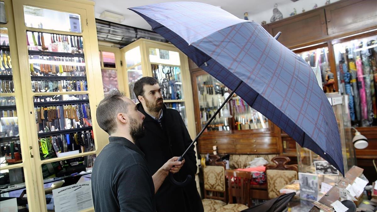 Toni Lama (en primer plano) ausculta el paraguas de un cliente en el local de Casa Lama.