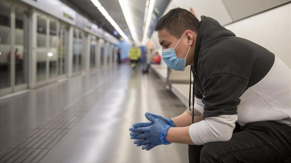 Un joven espera el metro en la estación de Sagrera, en Barcelona, con guantes y mascarilla.