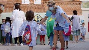 Una profesora saluda a sus alumnos en el primer día de colegio.