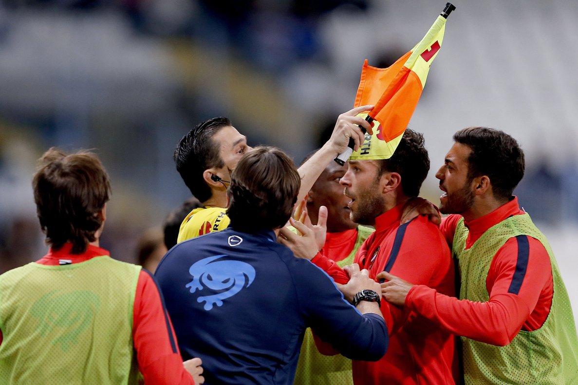 Jugadores de fútbol protestan ante un juez de línea que ha señalado un fuera de juego.