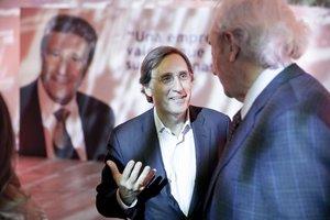 Tomás Pascual charla con Luis del Olmo en el acto del 50 aniversario de la firma Calidad Pascual celebrado en Barcelona. Al fondo la imagen del fundador Tomás Pascual (padre).