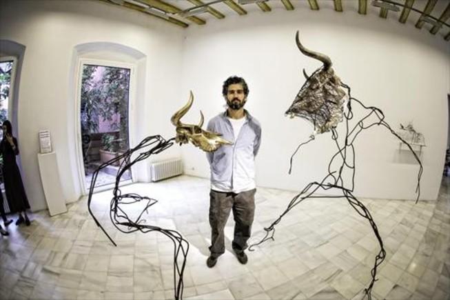 Álvaro Soler Arpa, entre dos de las esculturas de mayor tamaño de su exposición en la galería Miguel Marcos: un toro y una vaca en pleno reto.