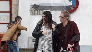 Vecinos de Melide (A Coruña) se protegen de la lluvia y el viento de la borrasca 'Ana'.
