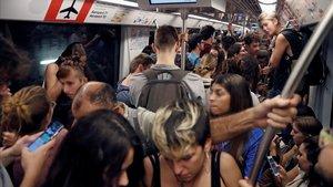 Centenares de personas se dirigen en metro al aeropuerto de El Prat, este lunes.