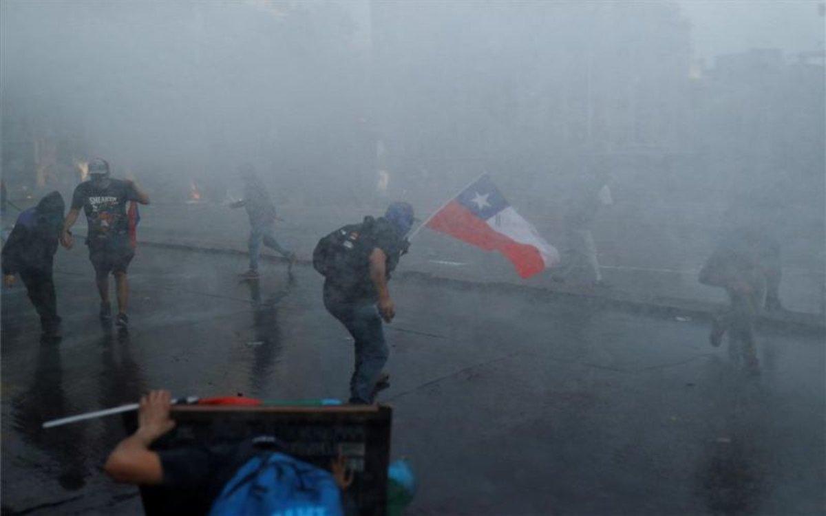 Los manifestantes en Chile se resguardan del ataque de la Polícia.