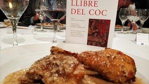 Un ejemplar de la nueva edición del Llibre del coc y una pularda con almendras.