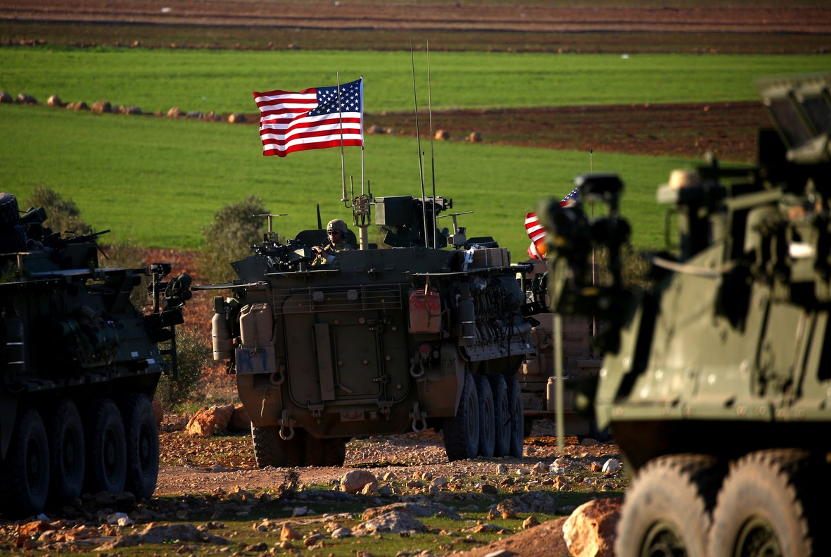 Un convoy de blindados con bandera de EEUU circulan por las afueras de la ciudad de Manbij, en el norte de Siria.