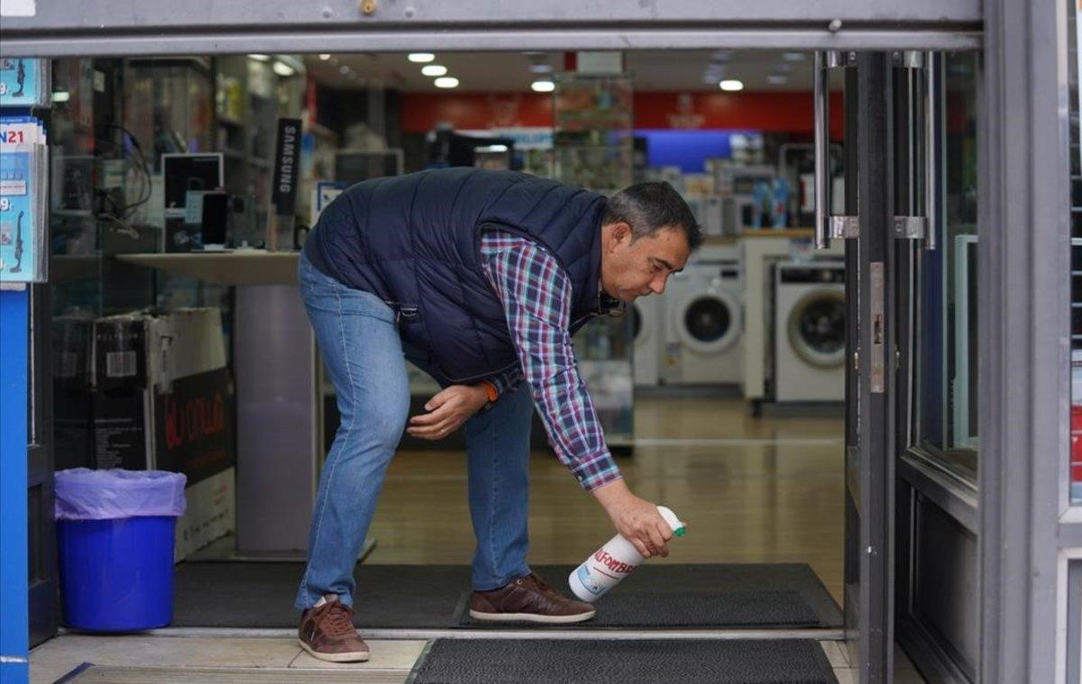 Un comerciante de Guadalajara, que el 11 de mayo entra en fase 1, desinfecta su comercio justo antes de abrirlo.
