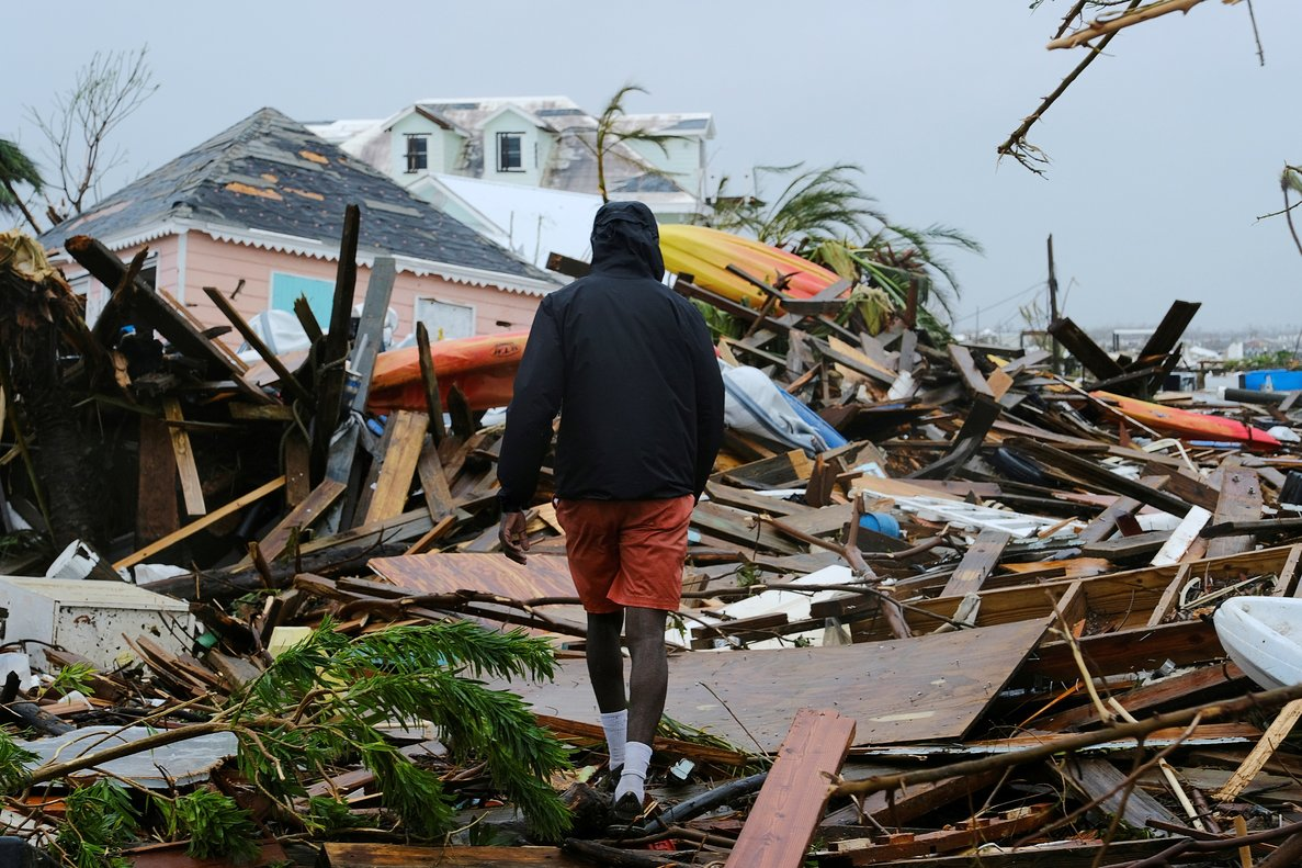 FILE PHOTO: A man walks through the rubble in the aftermath of Hurricane Dorian on the Great Abaco island town of Marsh Harbour, Bahamas, September 2, 2019. REUTERS/Dante Carrer/File Photo