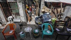 Una mujer espera una ración de comida en la barriada de Quezon, enManila.