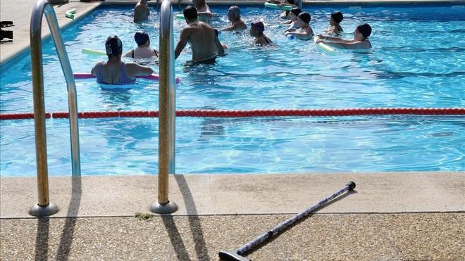 El bastón de Gabriela, fuera del agua, mientras ella disfruta en la piscina.