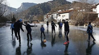 Un grup de joves juguen a futbol sobre la superfície gelada del riu Esca al seu pas per la localitat navarresa de Burgui.