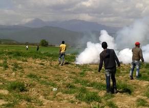 La guardia fronteriza macedonia lanza gases lacrimógenos contra los refugiados que intentaban cruzar la frontera desde Idomeni, este domingo.
