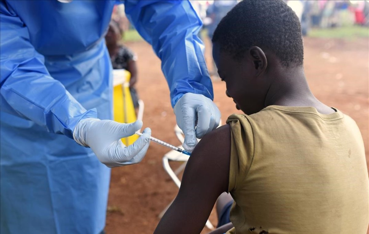 Un joven es vacunado contra el ébola por un médico congoleño.