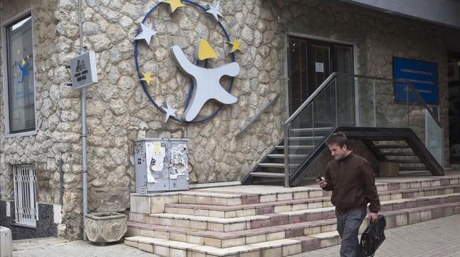 Un kosovar observa su móvil frente a la oficina cultural y de información de la UE en Pristina (Kosovo), este martes.