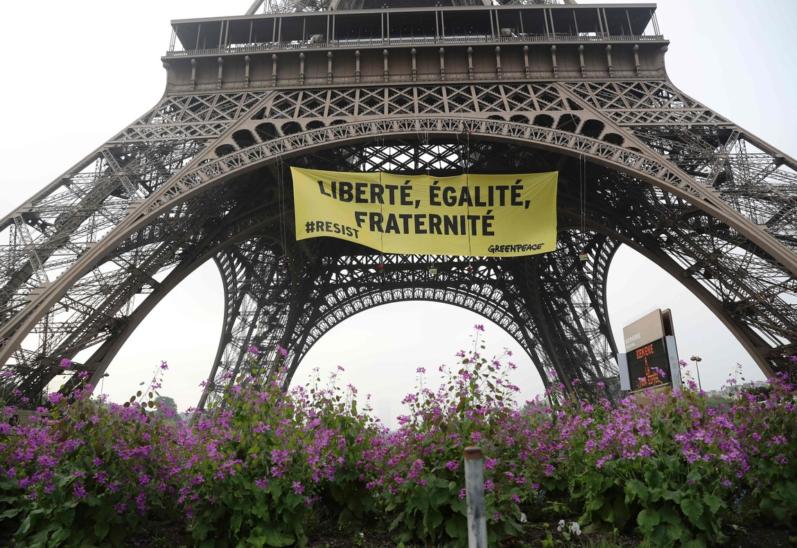 Libertad, igualdad, fraternidad, se lee en la pancarta que Greenpeace ha colgado en la Torre Eiffel.