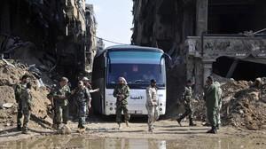 Militares del Ejército sirio supervisan un autobús que transporta combatientes vinculados a Al Qaeda durante una evacuación desde el campo de refugiados palestinos de Yarmuk, cerca de Damasco.