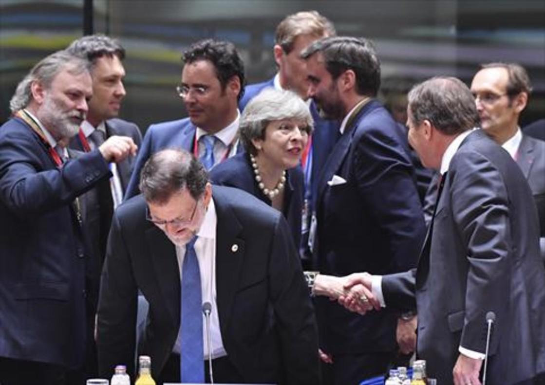 Rajoy, delante de May, toma asiento, durante la cumbre de ayer en Bruselas.