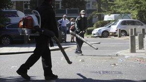 Voluntarios limpian las calles tras la batalla campal en el barrio de Brixton, en Londres.