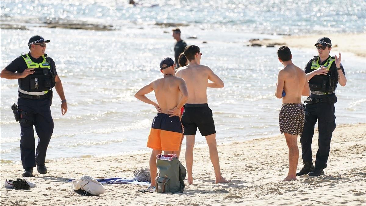 Unos policías advierten que los baños están prohibidos en una playa australiana.