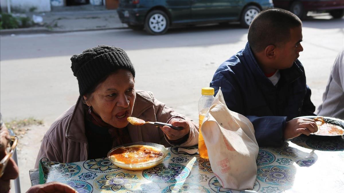 Una mujer y un hombre se alimentan en un comedor social de Villa Fiorito, en Buenos Aires, el pasado mes de junio.
