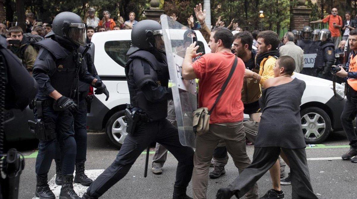 Policías intentando desalojar a personas concentradas ante el colegio Ramon Llull en Barcelona, el 1 de octubre del 2017.
