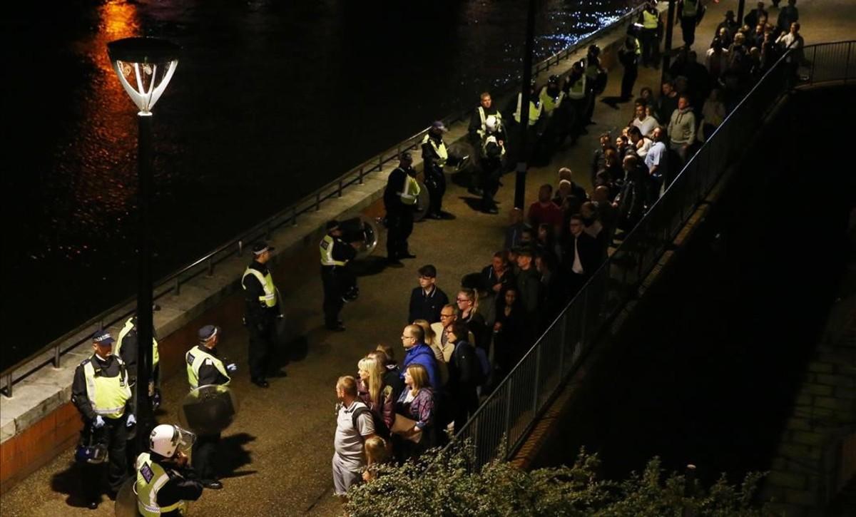 Agentes de policía paran ala gente evacuada de la zona del Puente de Londres.