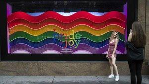Una chica posa delante de un escaparate neoyorkino decorado con la bandera LGBTI en ocasión del día del Orgullo y el desfile del Pride