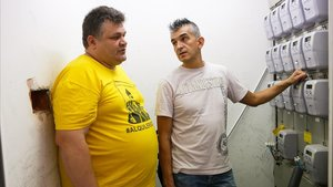 Rafael Julibert (camiseta amarilla)en el cuarto de contadores de la luz de uno de los pisos de la calle Falset, en Terrassa.