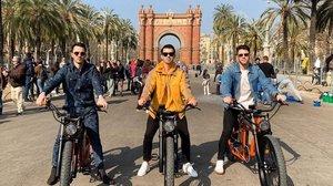 Los Jonas Brothers posan delante del Arc de Triomf tras un paseo en bici.