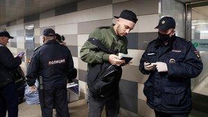 Agentes con máscaras vigilan las entradas en una estación de metro de Moscú.