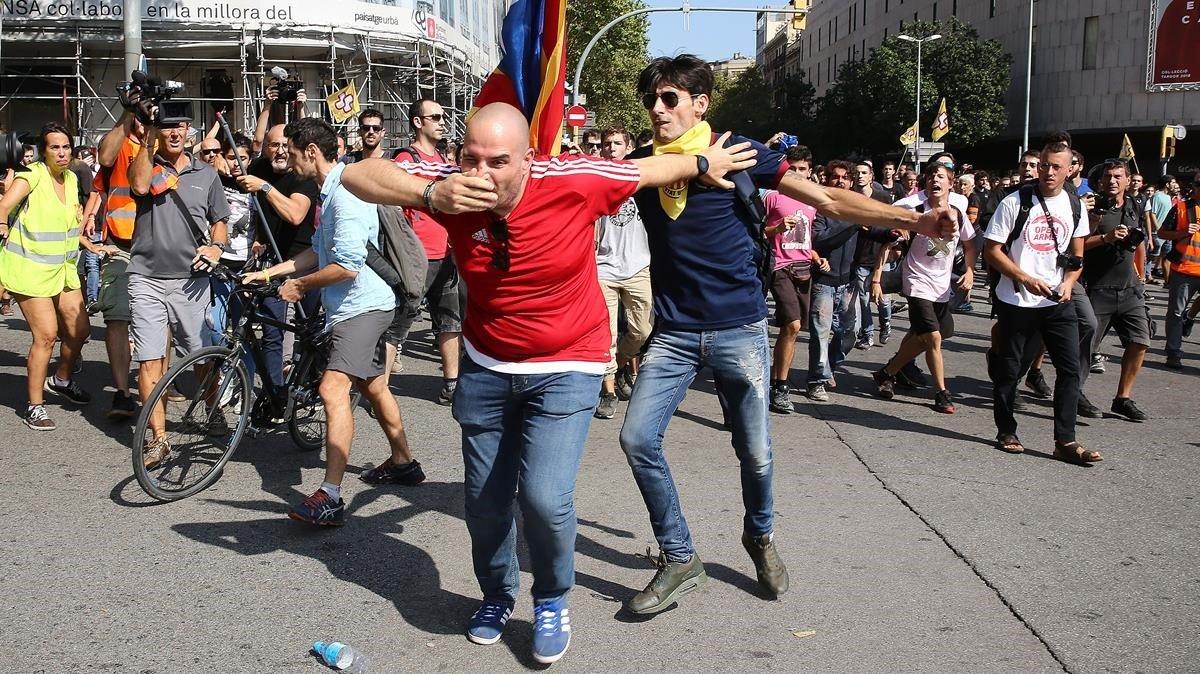 Un asistente a la manifestación de la Policía es agredido por un independentista, este sábado en Barcelona.