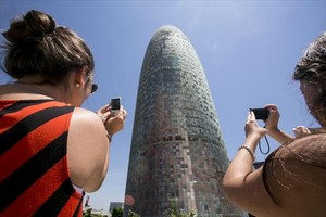 Dos turistas fotografían la torre Agbar.