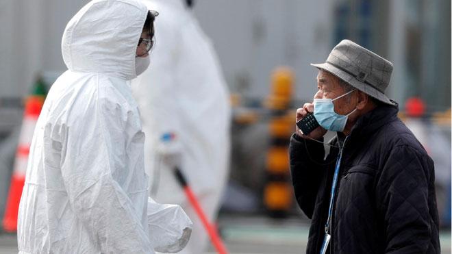 China eleva a 2.118 el número de muertos por el coronavirus entre los 74.576 infectados. En la foto, un pasajero desembarca del crucero Diamond Princess.