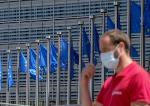 Brussels (Belgium), 25/05/2020.- A man wearing a face mask walks in front of the European Commission flags at the Berlaymont building headquarters in Brussels, Belgium, 25 May 2020. Countries around the world are gradually easing COVID-19 lockdown restrictions in an effort to restart the economy and help people in their daily routines. (Bélgica, Bruselas) EFE/EPA/OLIVIER HOSLET