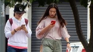 Dos chicas pasean por la calle sin hablarse y absortas en sus teléfonos móviles