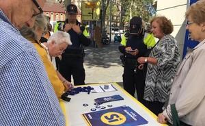 Dos guardias urbanos identifican a los miembros de una parada informativa sobre el referéndum, este sábado en Barcelona.