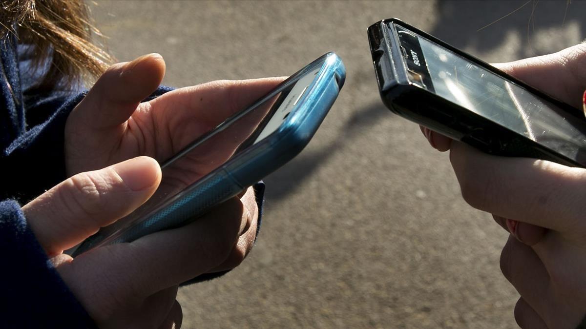 Dos jóvenes intercambiando información con sus teléfonos móviles.